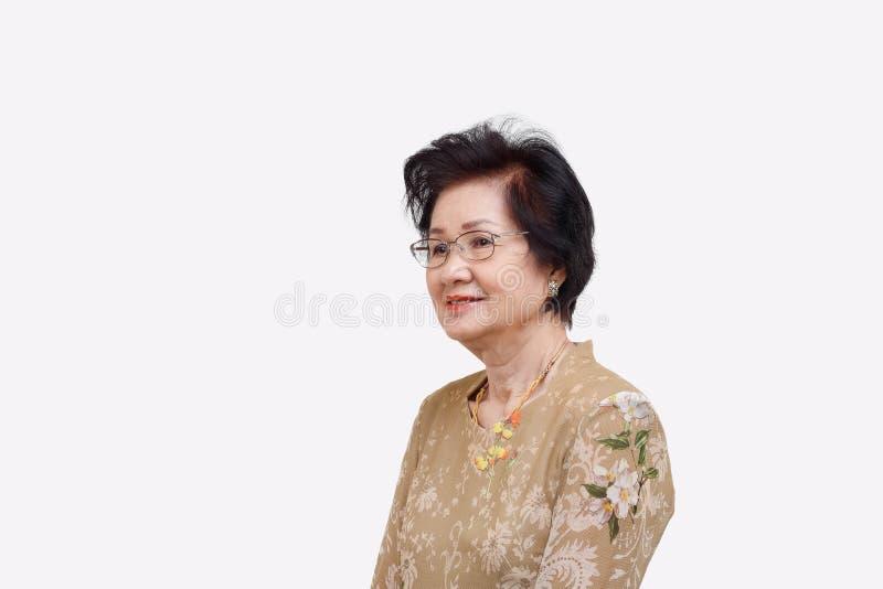 Szczęśliwa azjatykcia kobieta relaksuje w domu, odizolowywa na bielu obraz royalty free