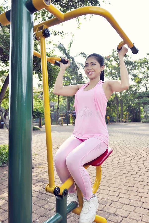 Szczęśliwa azjatykcia kobieta robi sprawność fizyczna treningowi z ciężarami maszynowymi zdjęcie stock