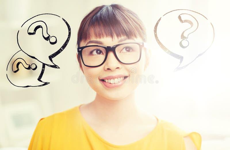 Szczęśliwa azjatykcia kobieta w szkłach nad znakami zapytania obraz stock