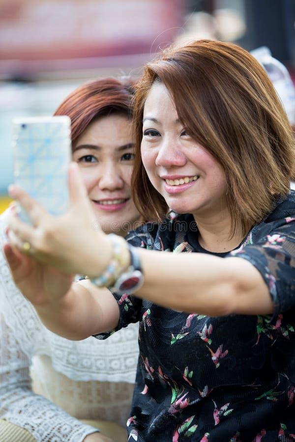 Download Szczęśliwa Azjatykcia Kobieta Z Przyjacielem Bierze Selfie Obraz Stock - Obraz złożonej z przyjaciele, lifestyle: 53779641
