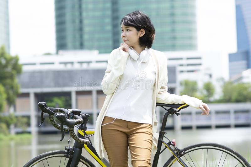 Szczęśliwa azjatykcia kobieta z rowerowym pobliskim jeziorem Rozmyty budynku tło fotografia royalty free