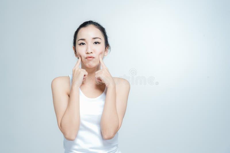 Szczęśliwa azjatykcia młoda kobieta piękna z myśl gesta posturą na białym tle zdjęcia royalty free