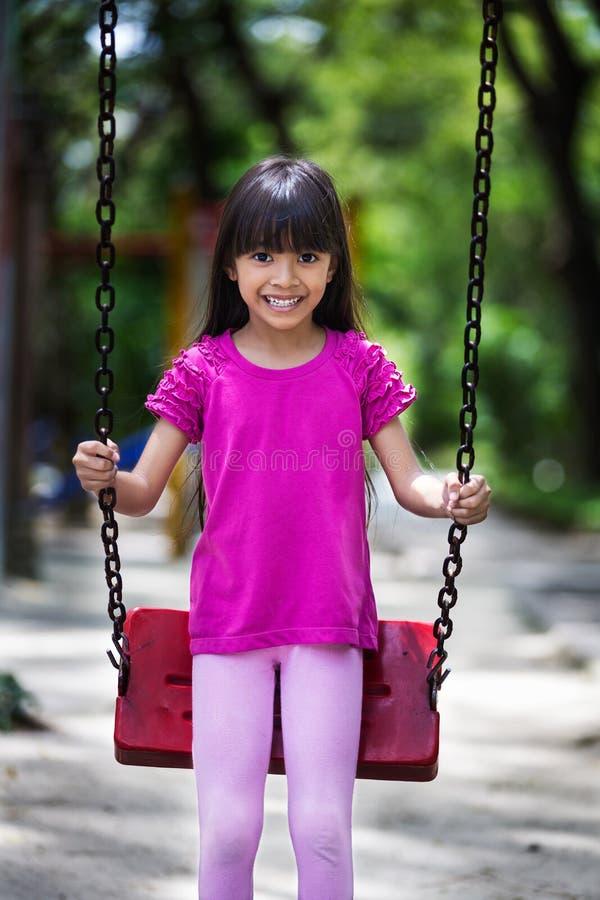Szczęśliwa azjatykcia mała dziewczynka ono uśmiecha się na huśtawce zdjęcia stock