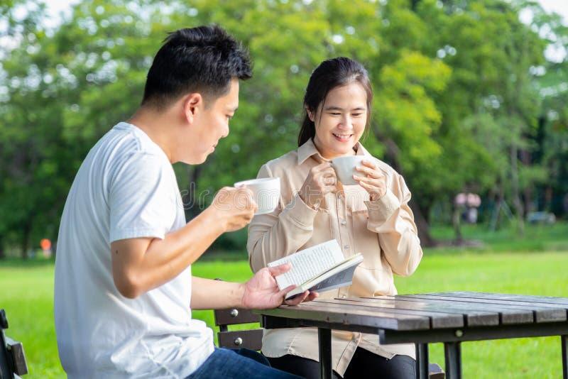 Szczęśliwa azjatykcia para cieszy się, opowiada wpólnie lub czyta książkę, ono uśmiecha się, żona napoju kawa, herbata w ranku lu obrazy royalty free