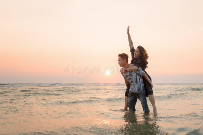 Szczęśliwa azjatykcia para ma zabawę na plaży przy zmierzchem fotografia royalty free