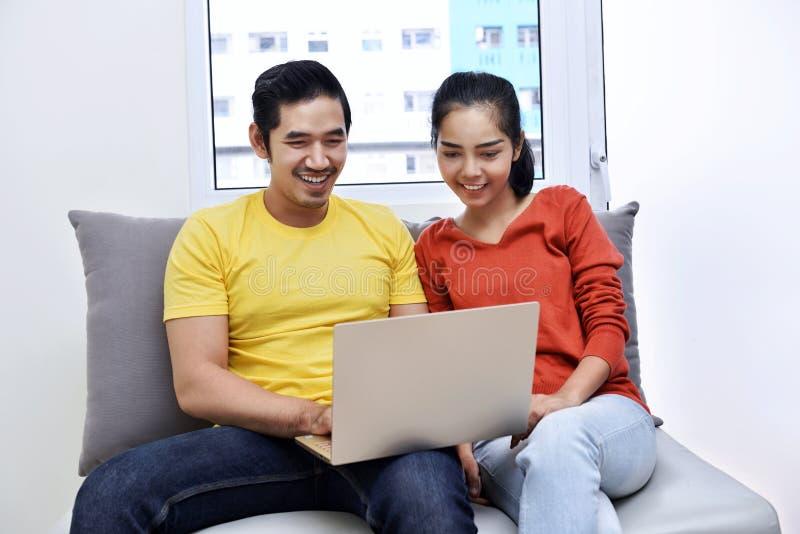 Szczęśliwa azjatykcia para używa laptop podczas gdy siedzący na leżance obrazy royalty free