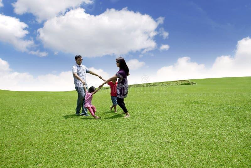 Szczęśliwa azjatykcia rodzina bawić się na polu obraz stock