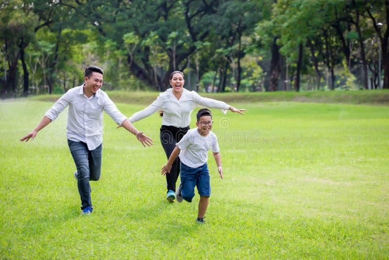 szczęśliwa azjatykcia rodzina, rodzice i ich dzieci biega wokoło w parku wpólnie, ojcuje matki i syna ma zabawę i śmiać się fotografia royalty free