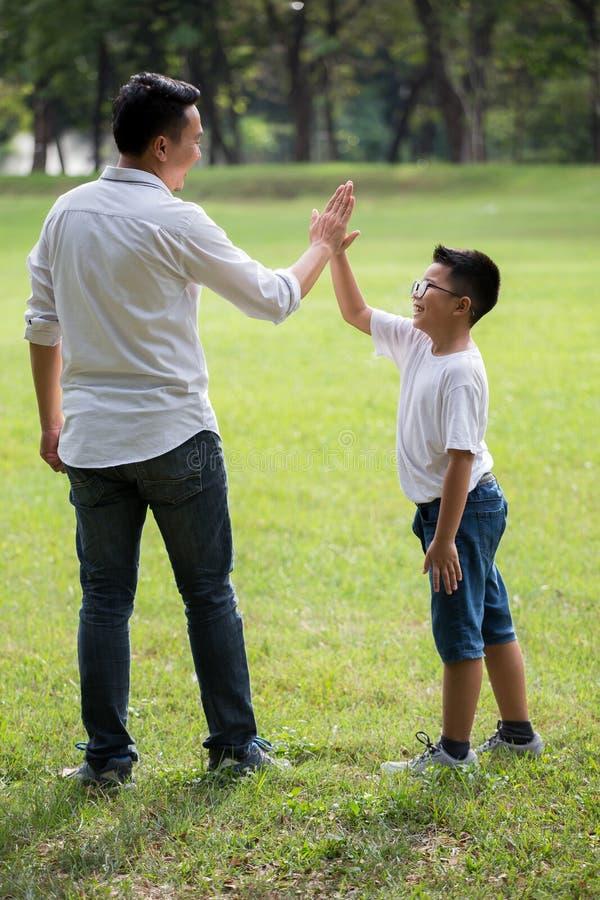 szczęśliwa azjatykcia rodzina, rodzice i ich dzieci, dajemy wysokości pięć w parku wpólnie ojca podporowy syn outside Poparcia po zdjęcie stock