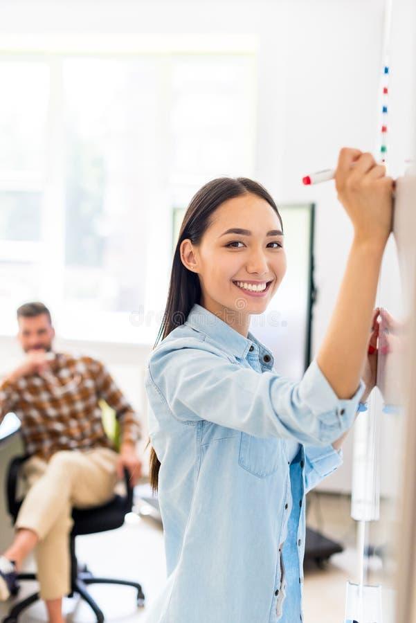 szczęśliwa azjatykcia studencka dziewczyna pisze na whiteboard podczas lekcji z zamazanym nauczycielem obraz stock