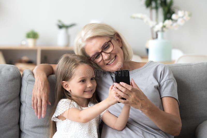 Szczęśliwa babcia i śliczna wnuczka używa telefonu komórkowego robić fotografia royalty free