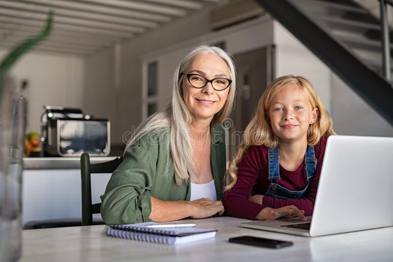 Szczęśliwa babcia i uśmiechnięta mała dziewczynka studiujemy w domu zdjęcie royalty free
