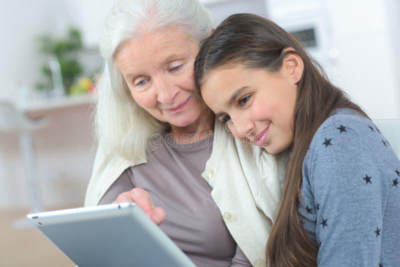 Szczęśliwa babcia z uroczystą córką patrzeje pastylkę zdjęcia stock