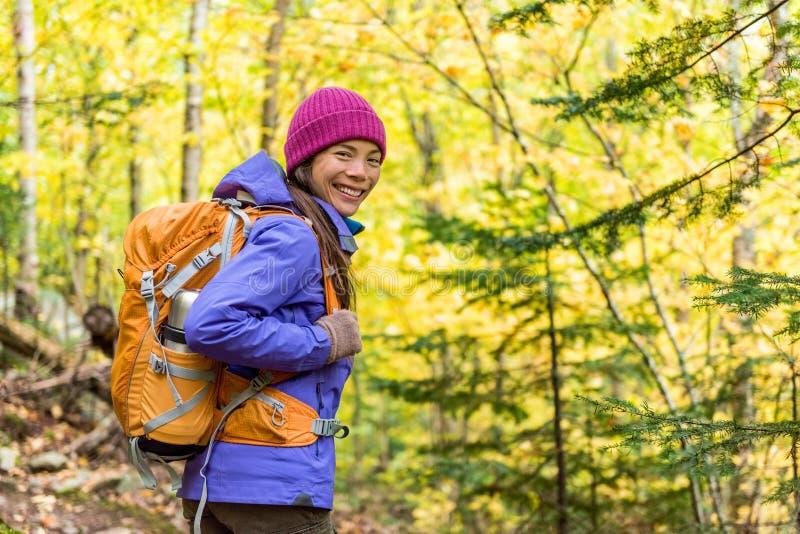 Szczęśliwa backpacker dziewczyna wycieczkuje w jesień wycieczkowicza lasowej Młodej azjatykciej kobiecie patrzeje w plenerowej pr zdjęcia royalty free
