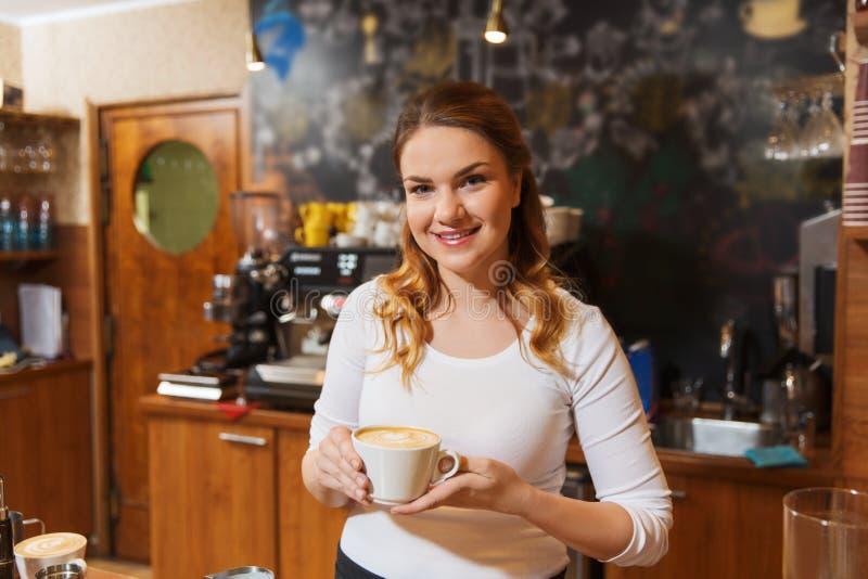 Szczęśliwa barista kobieta z latte przy sklep z kawą fotografia stock
