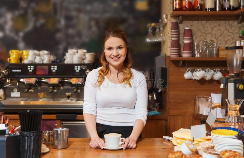 Szczęśliwa barista kobieta z latte przy sklep z kawą zdjęcia royalty free