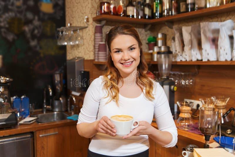 Szczęśliwa barista kobieta z latte przy sklep z kawą obrazy stock