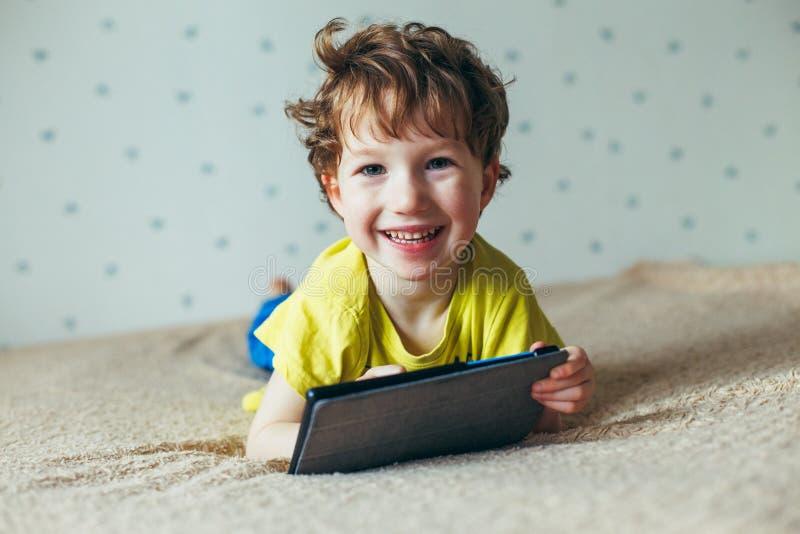 Szczęśliwa berbeć chłopiec ma zabawę bawić się grę na gadżecie, Preschool dzieciaka sititng na kanapie z uśmiechniętą twarzy dopa zdjęcia stock