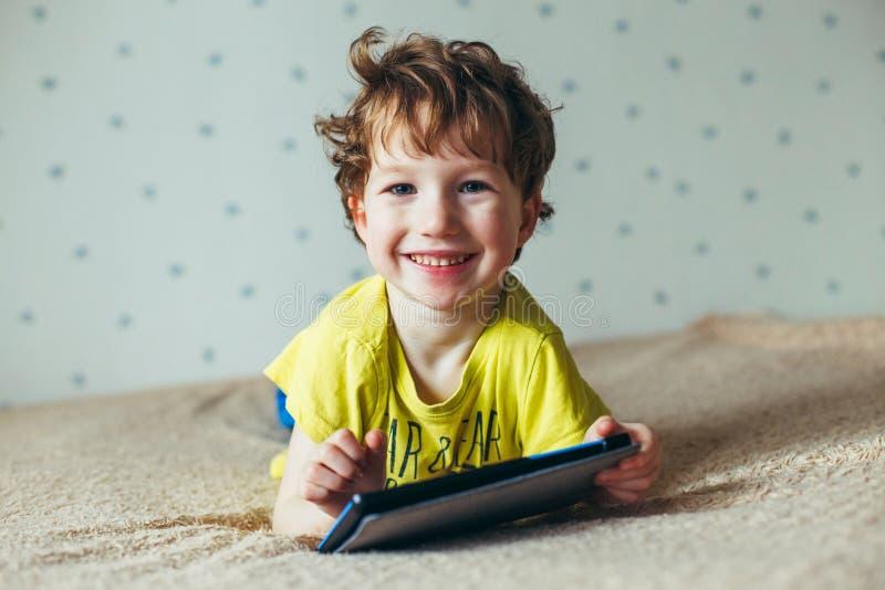 Szczęśliwa berbeć chłopiec ma zabawę bawić się grę na gadżecie, Preschool dzieciaka sititng na kanapie z uśmiechniętą twarzy dopa fotografia royalty free