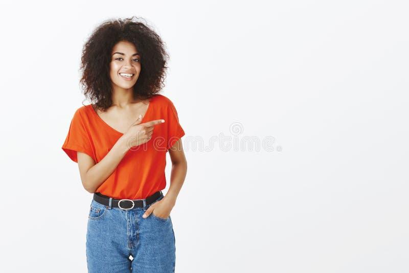 Szczęśliwa beztroska amerykanin afrykańskiego pochodzenia kobieta ono uśmiecha się szeroko z kędzierzawą fryzurą podczas gdy wska zdjęcia royalty free