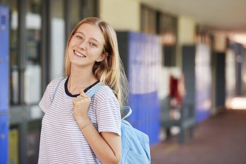 Szczęśliwa biała nastoletnia dziewczyna ono uśmiecha się w szkoła średnia korytarzu obrazy stock