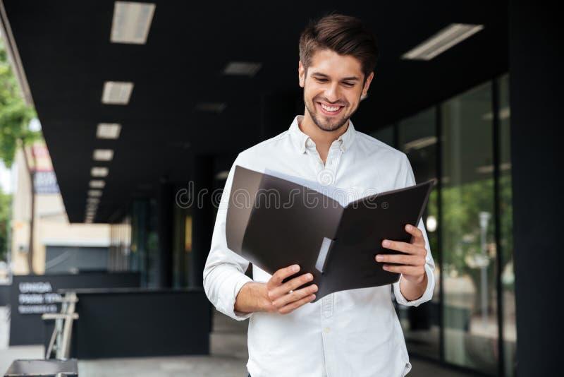 Szczęśliwa biznesmen pozycja i patrzeć przez dokumentów w falcówce obraz royalty free