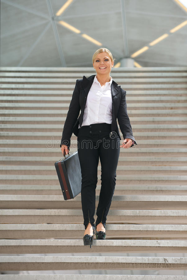 Szczęśliwa biznesowa kobieta chodzi downstairs z teczką zdjęcie royalty free