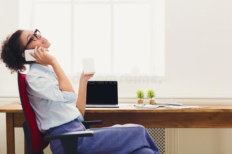 Szczęśliwa biznesowa kobieta opowiada na telefonie przy pracą obrazy stock