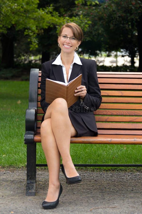 Szczęśliwa biznesowa kobieta pisze w jej notatniku w parku fotografia stock