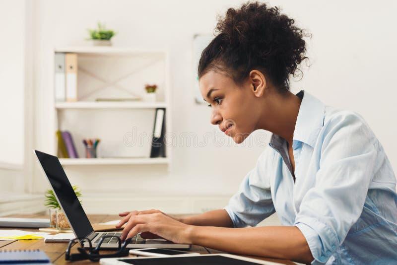 Szczęśliwa biznesowa kobieta pracuje na laptopie przy biurem obrazy stock