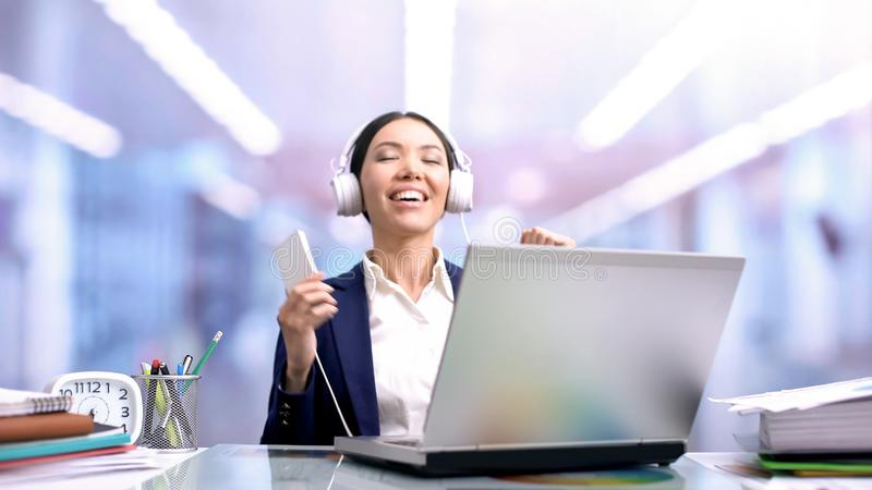 Szczęśliwa biznesowa kobieta słucha muzyka w hełmofonach podczas pracy przerwy, odpoczynek fotografia royalty free