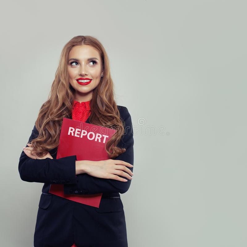 Szczęśliwa biznesowa kobieta trzyma biznesowego raport przeciw biel ściany tłu fotografia stock