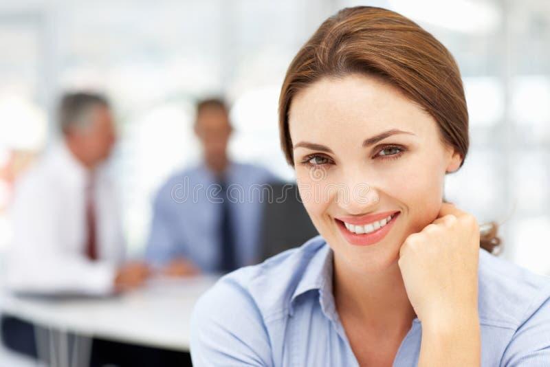 Szczęśliwa biznesowa kobieta w biurze z kolegami zdjęcia stock