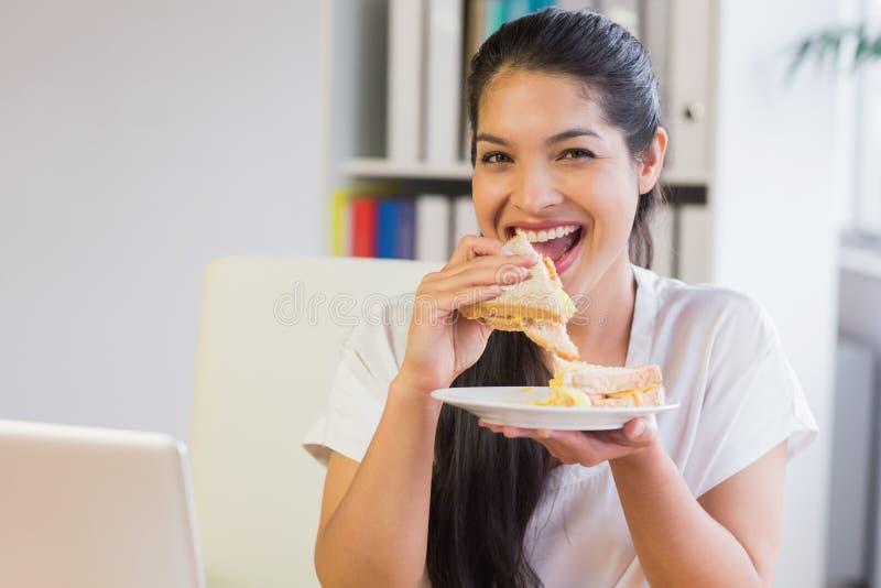Szczęśliwa bizneswomanu łasowania kanapka obrazy royalty free