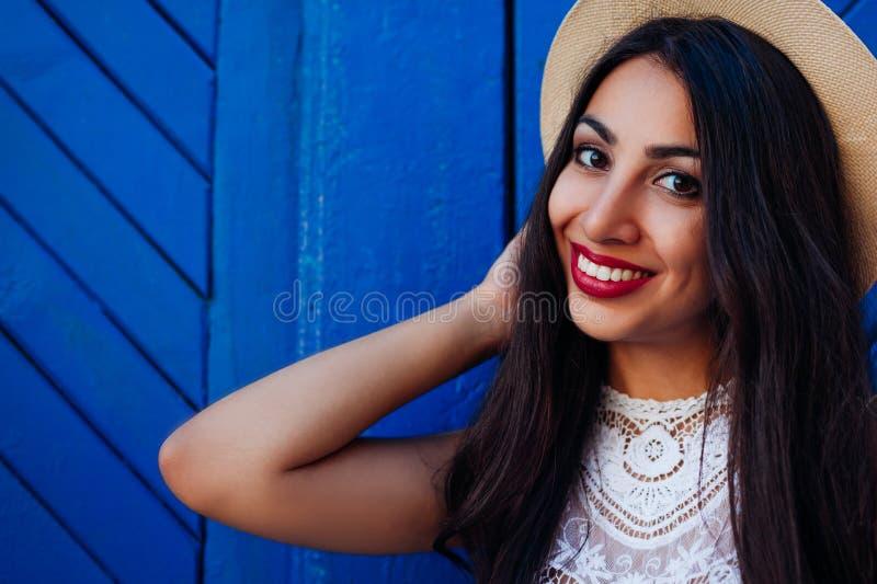Szczęśliwa bliskowschodnia dziewczyna uśmiechnięta i patrzeje kamerę Plenerowy portret jest ubranym lato kapelusz młoda kobieta zdjęcia royalty free
