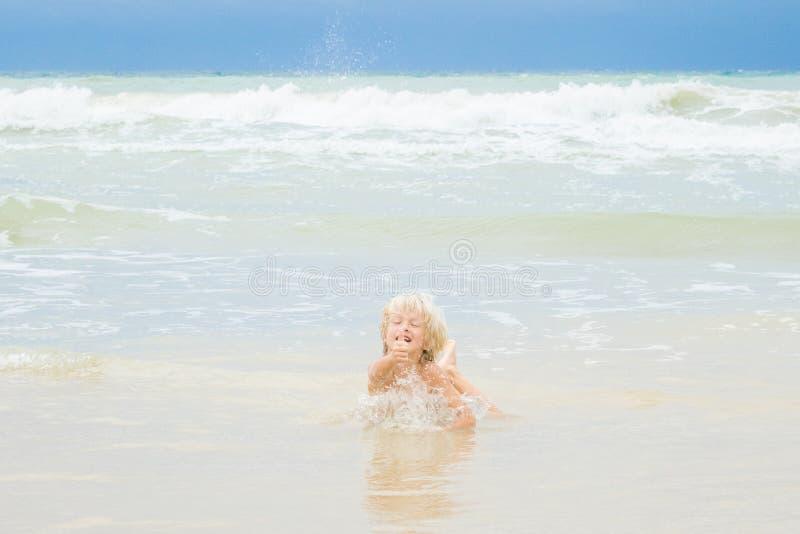 Szczęśliwa blond chłopiec kłama w wodzie na plaży, Wietnam, Nha-trang zdjęcia stock