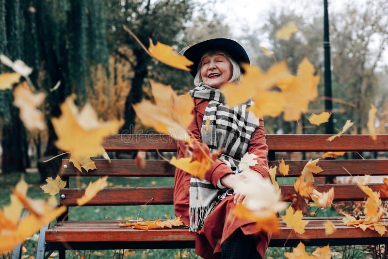 Szczęśliwa blondynka przechodzić na emeryturę żeński obsiadanie na ławce fotografia stock