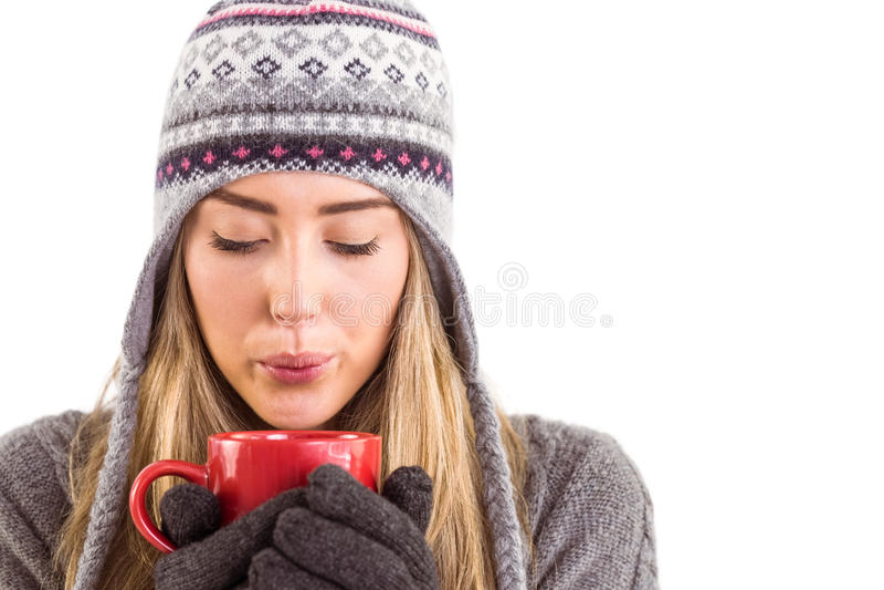 Szczęśliwa blondynka w zimy mienia odzieżowym kubku zdjęcia royalty free