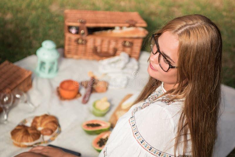 Szczęśliwa blondynka z okularami z piknikiem na zewnÄ…trz, na trawie zdjęcia royalty free
