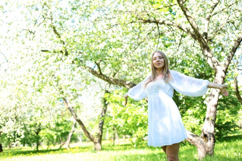Szczęśliwa blondynki kobieta na tle kwitnący wiosna ogród z ona ręki podnosić niebo zdjęcie royalty free