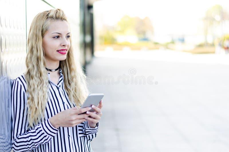 Szczęśliwa blondynki młoda kobieta plenerowa używać jej telefon komórkowego odizolowywającego fotografia royalty free