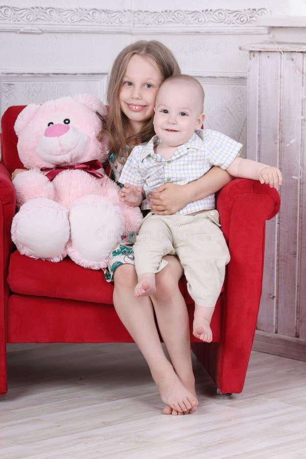 Szczęśliwa bosa mała dziewczynka w sukni i jej bracie fotografia stock