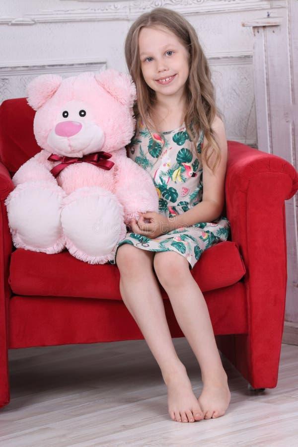 Szczęśliwa bosa mała dziewczynka w sukni siedzi z zabawką obraz stock
