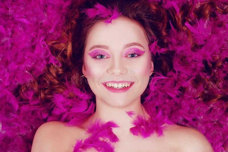 Szczęśliwa brunetka się uśmiecha Dziewczyna kłamie na tle fioletowych piór, różowe tło Dziewczyna z pięknym roamem / fioletowy zdjęcie stock