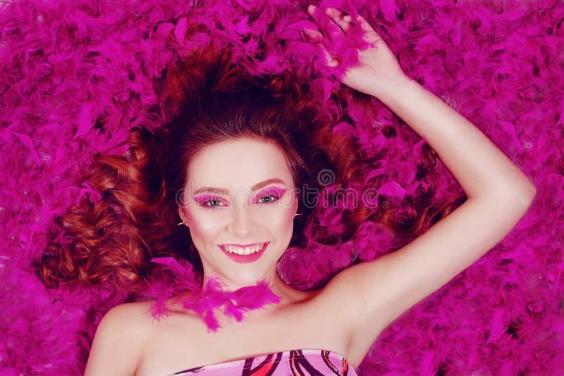 Szczęśliwa brunetka się uśmiecha Dziewczyna kłamie na tle fioletowych piór, różowe tło Dziewczyna z pięknym roamem / fioletowy obraz royalty free