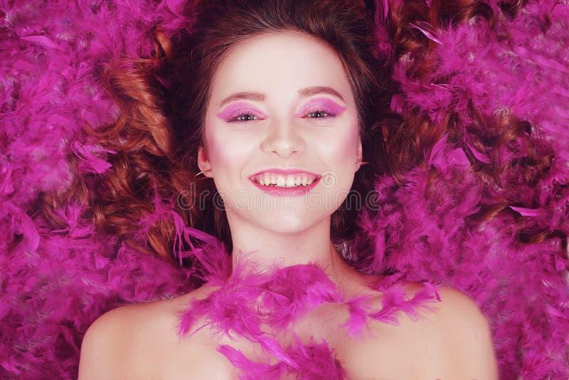 Szczęśliwa brunetka się uśmiecha Dziewczyna Leżin na tle fioletowych piór, różowe tło Dziewczynka z pięknym roamem zdjęcia stock