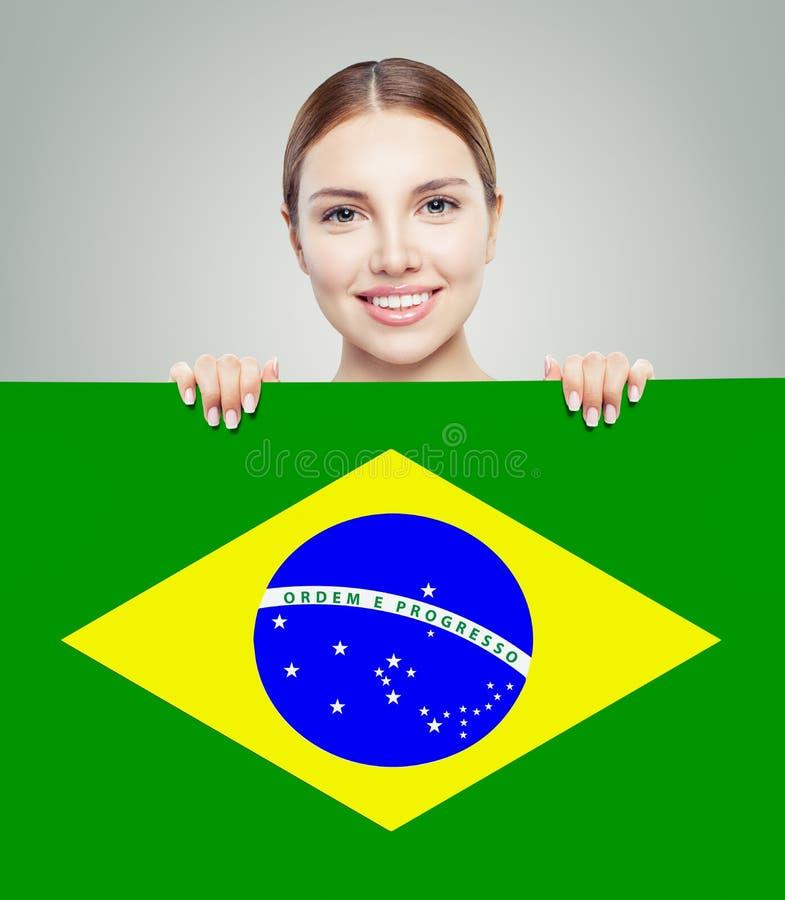 Szczęśliwa brunetki dziewczyna z Brazylia flagi tłem zdjęcia royalty free