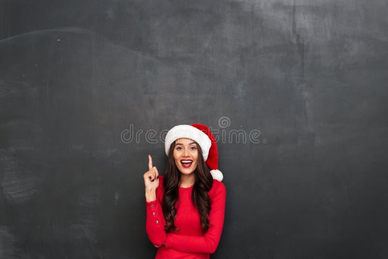 Szczęśliwa brunetki kobieta w czerwonej bluzce i bożych narodzeniach kapeluszowych zdjęcie stock