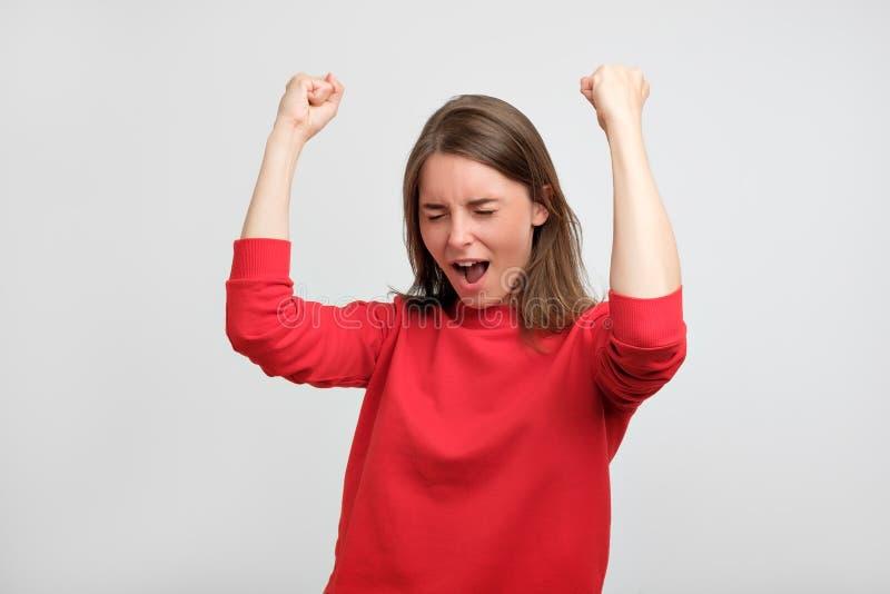 Szczęśliwa caucasian kobieta w czerwonym pulowerze exults pompujący pięść świętuje sukces lub zwycięstwo fotografia royalty free