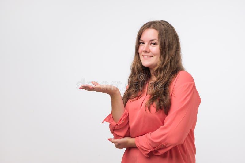 Szczęśliwa caucasian młoda kobieta ono uśmiecha się szeroko przy kamerą w pulowerze, wskazujący dotyka daleko od, pokazywać coś c zdjęcie royalty free